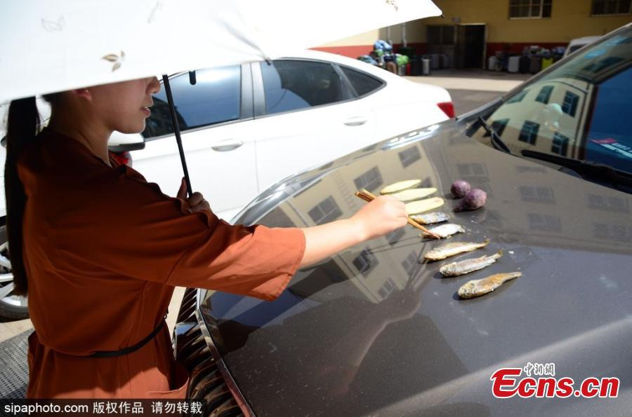 A woman grills fish, meat, potato slices and sweet potato on the bonnet of a car in Binzhou City, East China's Shandong Province, June 5, 2018, as temperatures rise to nearly 40 degrees centigrade. It took half an hour to cook the fish. (Photo/SipaPhoto)