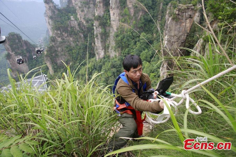 Sanitary worker Liu Wenhua collects garbage on a cliff while hanging from a cable at Wulingyuan scenic area in Zhangjiajie City, Central China's Hunan Province, June 5, 2018. Liu, 48, has worked at the tourist attraction for nearly five years, mainly responsible for cleaning litter left by irresponsible visitors. (Photo: China News Service/Wu Yongbing)