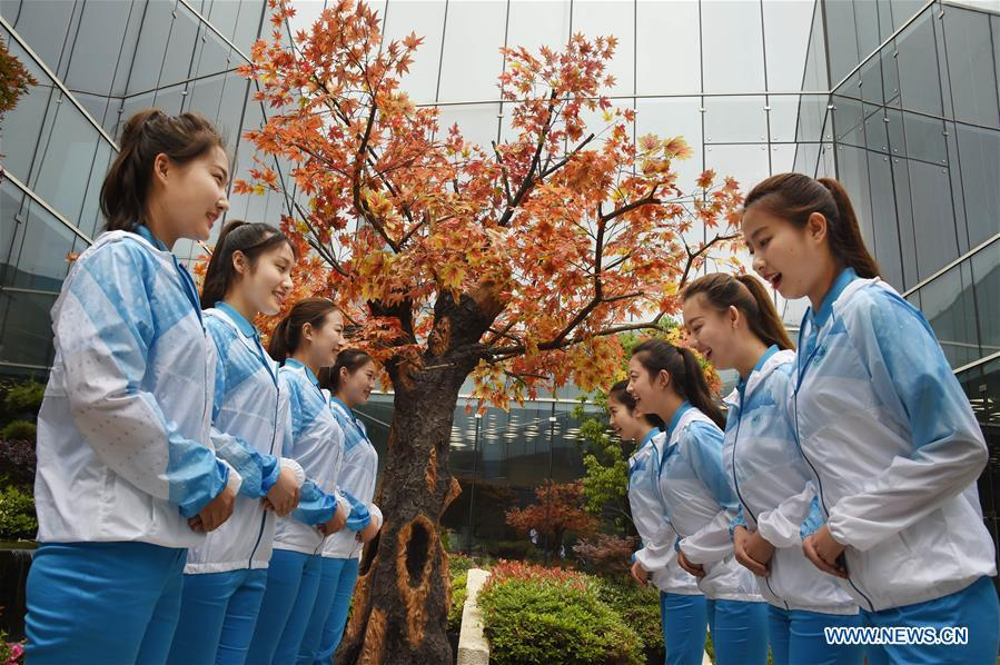 Eight etiquette volunteers for the 18th Shanghai Cooperation Organization (SCO) Summit practice in Qingdao, east China\'s Shandong Province, June 5, 2018. More than 20,000 volunteers have been mobilized to offer services for the summit, from assisting with guests\' arrival and departure, translation, and media requests, to the operation of city functions such as transportation, telecommunication, and banks. (Xinhua/Li Ziheng)