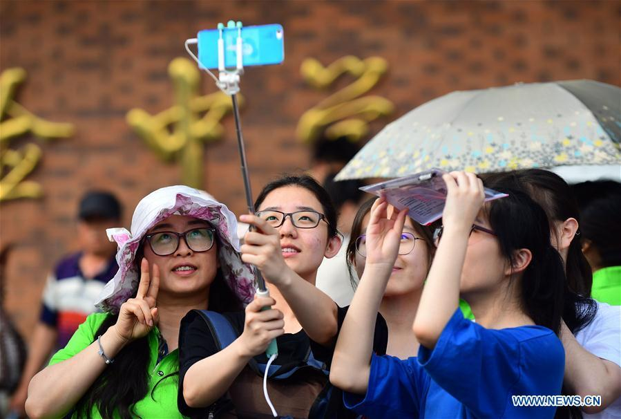 Examinees take a selfie with their family before the national college entrance examination outside an exam venue in Changchun, northeast China\'s Jilin Province, June 7, 2018. About 9.75 million students have registered for the national college entrance examination, which takes place from June 7 to 8. (Xinhua/Lin Hong)