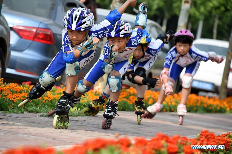 Children practice roller skating in Qingdao, east China\'s Shandong Province, June 4, 2018. The 18th Shanghai Cooperation Organization (SCO) Summit is scheduled for June 9 to 10 in Qingdao. (Xinhua/Li Ziheng)