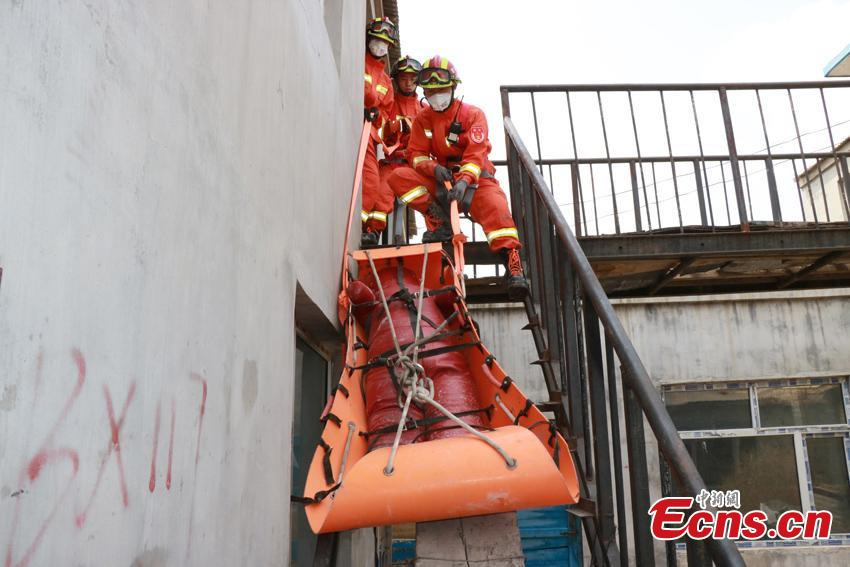 Firefighting authorities in Changchun City, Northeast China's Jilin Province organized an earthquake drill focusing on search and rescue. Some 90 officers, assisted by search dogs and advanced devices, tested their knowledge and skills in quake emergency responses through different scenarios, such as removing building debris with machines. (Photo: China News Service/Ma Xuewen)