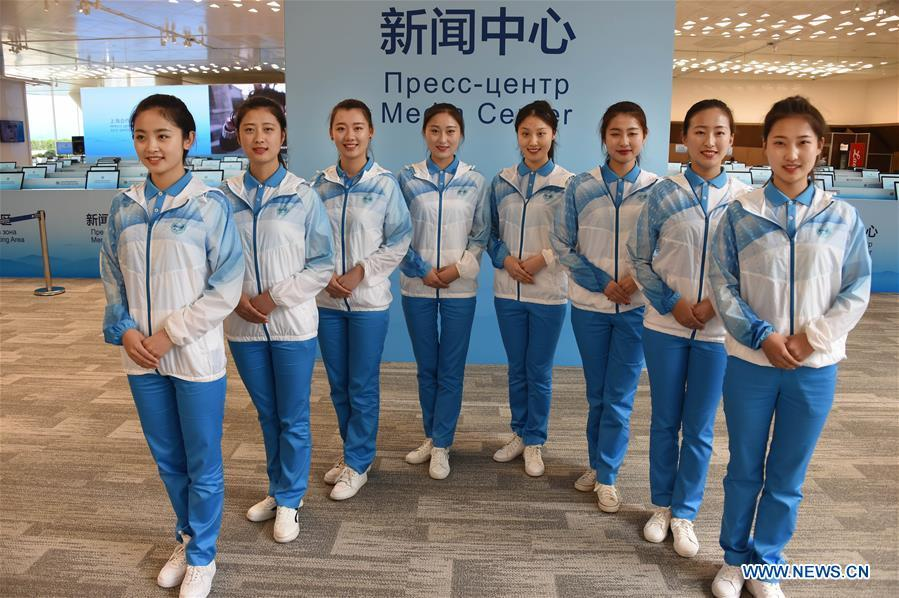 Eight etiquette volunteers pose for a photo at the media center for the 18th Shanghai Cooperation Organization (SCO) Summit in Qingdao, east China\'s Shandong Province, June 5, 2018. More than 20,000 volunteers have been mobilized to offer services for the summit, from assisting with guests\' arrival and departure, translation, and media requests, to the operation of city functions such as transportation, telecommunication, and banks. (Xinhua/Li Ziheng)