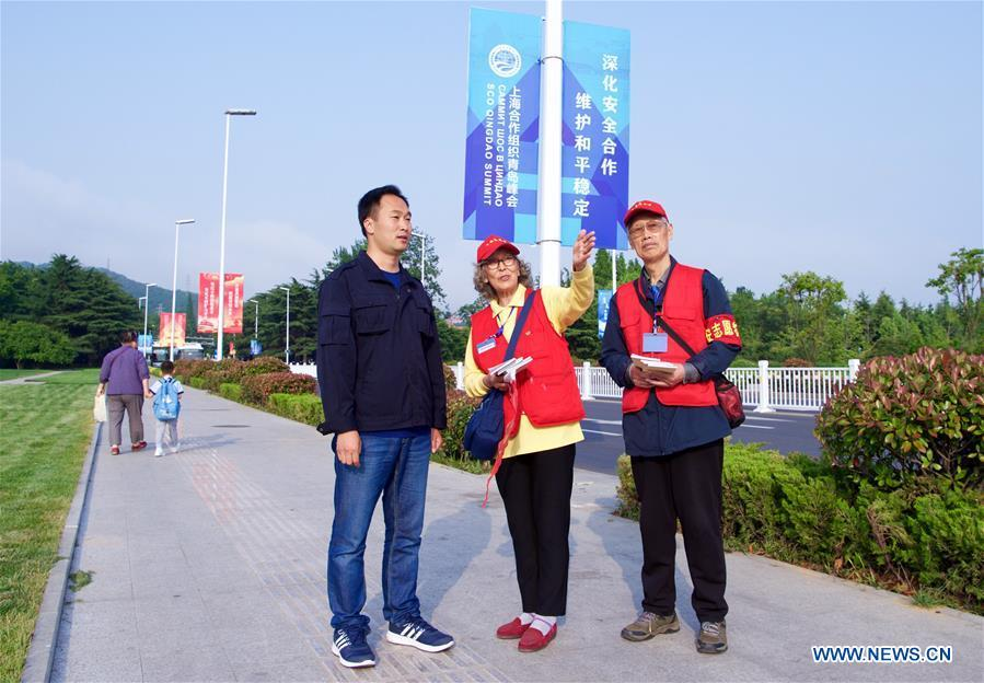 Jiang Shifa (R) and his wife Lian Shifang, volunteers for the Shanghai Cooperation Organization (SCO) Qingdao Summit, guide a tourist in Wendeng Road in Qingdao, east China\'s Shandong Province, June 5, 2018. Jiang, 74 years old and his wife, 72 years old, have been volunteers for over ten years after retired from work. The couple feel thrilled to be volunteers for the upcoming SCO Qingdao Summit ten years after they served as volunteers for the Beijing 2008 Olympic Games Sailing event in Qingdao. (Xinhua/Jiang Kehong)