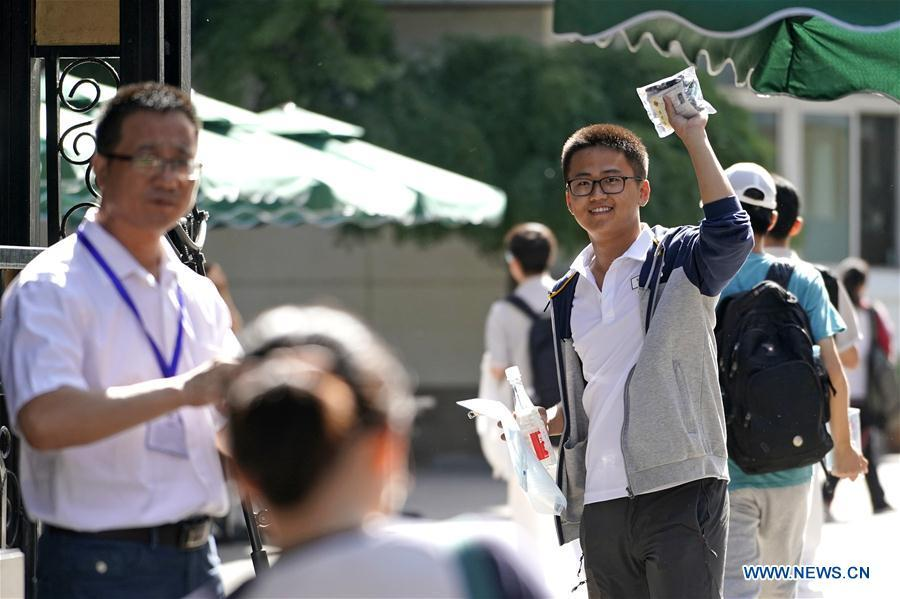 An examinee waves to his family at the exam venue at Beijing No. 4 High School in Beijing, capital of China, June 7, 2018. About 9.75 million students have registered for the national college entrance examination, which takes place from June 7 to 8. (Xinhua/Shen Bohan)