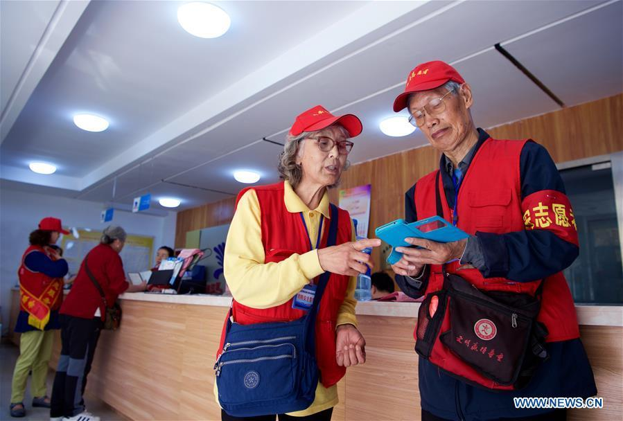 Jiang Shifa (R) and his wife Lian Shifang, volunteers for the Shanghai Cooperation Organization (SCO) Qingdao Summit, gather at Mingxialu Community for training in Qingdao, east China\'s Shandong Province, June 5, 2018. Jiang, 74 years old and his wife, 72 years old, have been volunteers for over ten years after retired from work. The couple feel thrilled to be volunteers for the upcoming SCO Qingdao Summit ten years after they served as volunteers for the Beijing 2008 Olympic Games Sailing event in Qingdao. (Xinhua/Jiang Kehong)