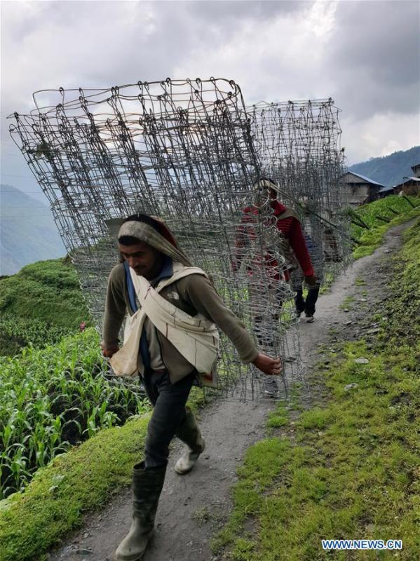 People carry iron nets used for construction at Chhomrong village of Kaski district in Nepal, June 6, 2018. (Xinhua/Sunil Sharma)