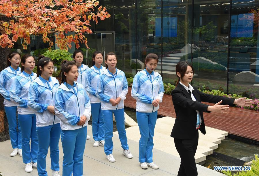 Etiquette teacher Lu Min (1st R) instructs volunteers for the 18th Shanghai Cooperation Organization (SCO) Summit in Qingdao, east China\'s Shandong Province, June 5, 2018. More than 20,000 volunteers have been mobilized to offer services for the summit, from assisting with guests\' arrival and departure, translation, and media requests, to the operation of city functions such as transportation, telecommunication, and banks. (Xinhua/Li Ziheng)