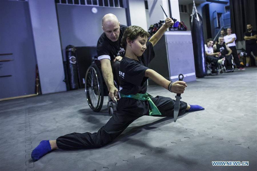 Kostas Moukas (back), a disabled Wushu teacher, teaches in his wheelchair, in Athens, Greece, June 5, 2018. Kostas Moukas started practicing Wushu since 2003 and is the only Wushu teacher in a wheelchair in Greece. He trains mixed classes that include seven disabled athletes who compete officially in the national championships. (Xinhua/Panagiotis Moschandreou)
