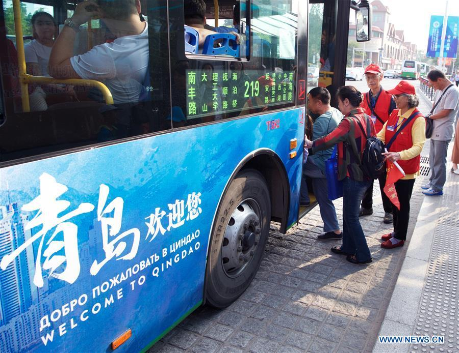 Jiang Shifa (3rd R) and his wife Lian Shifang (2nd R), volunteers for the Shanghai Cooperation Organization (SCO) Qingdao Summit, guide passengers at a bus stop in Qingdao, east China\'s Shandong Province, June 5, 2018. Jiang, 74 years old and his wife, 72 years old, have been volunteers for over ten years after retired from work. The couple feel thrilled to be volunteers for the upcoming SCO Qingdao Summit ten years after they served as volunteers for the Beijing 2008 Olympic Games Sailing event in Qingdao. (Xinhua/Jiang Kehong)