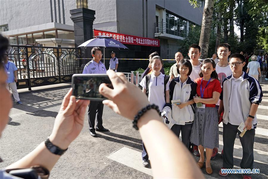 Examinees pose for a group photo outside the exam venue at Beijing No. 4 High School in Beijing, capital of China, June 7, 2018. About 9.75 million students have registered for the national college entrance examination, which takes place from June 7 to 8. (Xinhua/Shen Bohan)