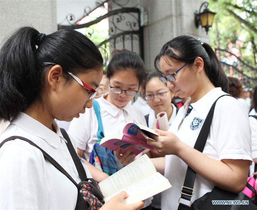 Examinees review lessons outside the exam venue at Shanghai No. 54 High School in Shanghai, east China, June 7, 2018. About 9.75 million students have registered for the national college entrance examination, which takes place from June 7 to 8. (Xinhua/Xu Xiaoxuan)