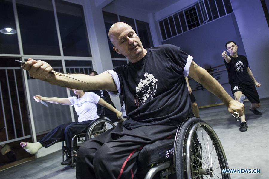 Kostas Moukas (front), a disabled Wushu teacher, teaches in his wheelchair, in Athens, Greece, June 5, 2018. Kostas Moukas started practicing Wushu since 2003 and is the only Wushu teacher in a wheelchair in Greece. He trains mixed classes that include seven disabled athletes who compete officially in the national championships. (Xinhua/Panagiotis Moschandreou)