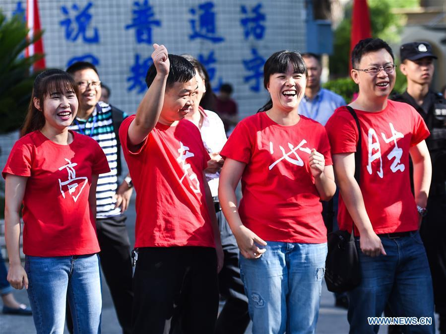 Teachers encourage examinees at an exam venue in Guiyang, capital of southwest China\'s Guizhou Province, June 7, 2018. About 9.75 million students have registered for the national college entrance examination, which takes place from June 7 to 8. (Xinhua/Tao Liang)