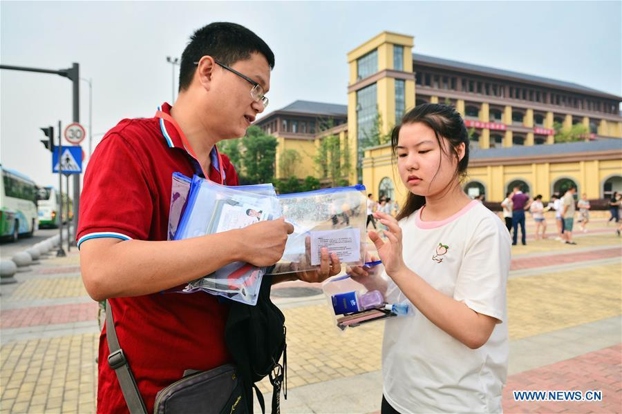A teacher distributes ID cards and stationery to examinees at an exam venue in Chengdu, capital of southwest China\'s Sichuan Province, June 7, 2018. About 9.75 million students have registered for the national college entrance examination, which takes place from June 7 to 8. (Xinhua/Jiang Hongjing)