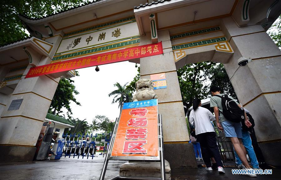 Examinees enter an exam venue at Hainan Middle School in Haikou, capital of south China\'s Hainan Province, June 7, 2018. About 9.75 million students have registered for the national college entrance examination, which takes place from June 7 to 8. (Xinhua/Guo Cheng)