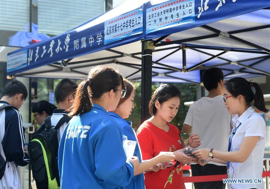 A staff member checks the credentials of examinees at an exam venue in Beijing, capital of China, June 7, 2018. About 9.75 million students have registered for the national college entrance examination, which takes place from June 7 to 8. (Xinhua/Luo Xiaoguang)