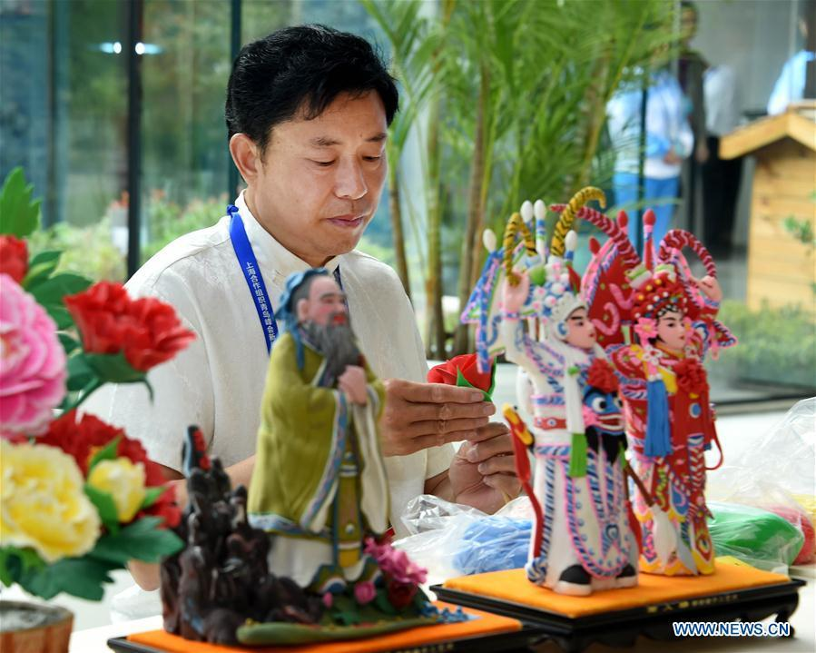 Craftsman Mu Xujian makes dough sculptures at the media center for the 18th Shanghai Cooperation Organization (SCO) Summit in Qingdao, east China\'s Shandong Province, June 6, 2018. (Xinhua/Li Ziheng)