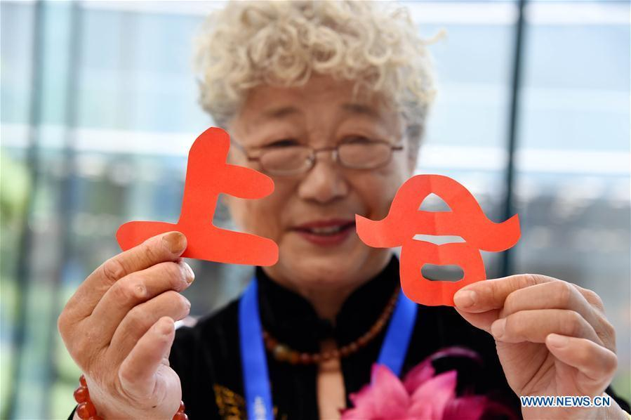 Craftswoman Li Wenling shows her paper-cutting works at the media center for the 18th Shanghai Cooperation Organization (SCO) Summit in Qingdao, east China\'s Shandong Province, June 6, 2018. (Xinhua/Li Ziheng)