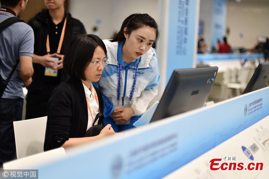 Volunteers work at the press center of the Shanghai Cooperation Organization Qingdao Summit in Qingdao City, East China's Shandong Province, June 7, 2018. Some 370 volunteers from four universities in Qingdao are assisting journalists from home and abroad at the press center. (Photo/VCG)