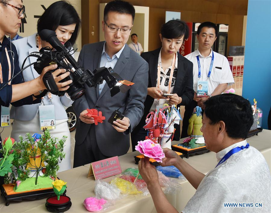 Craftsman Mu Xujian shows dough sculpture making to journalists at the media center for the 18th Shanghai Cooperation Organization (SCO) Summit in Qingdao, east China\'s Shandong Province, June 6, 2018. (Xinhua/Guo Xulei)
