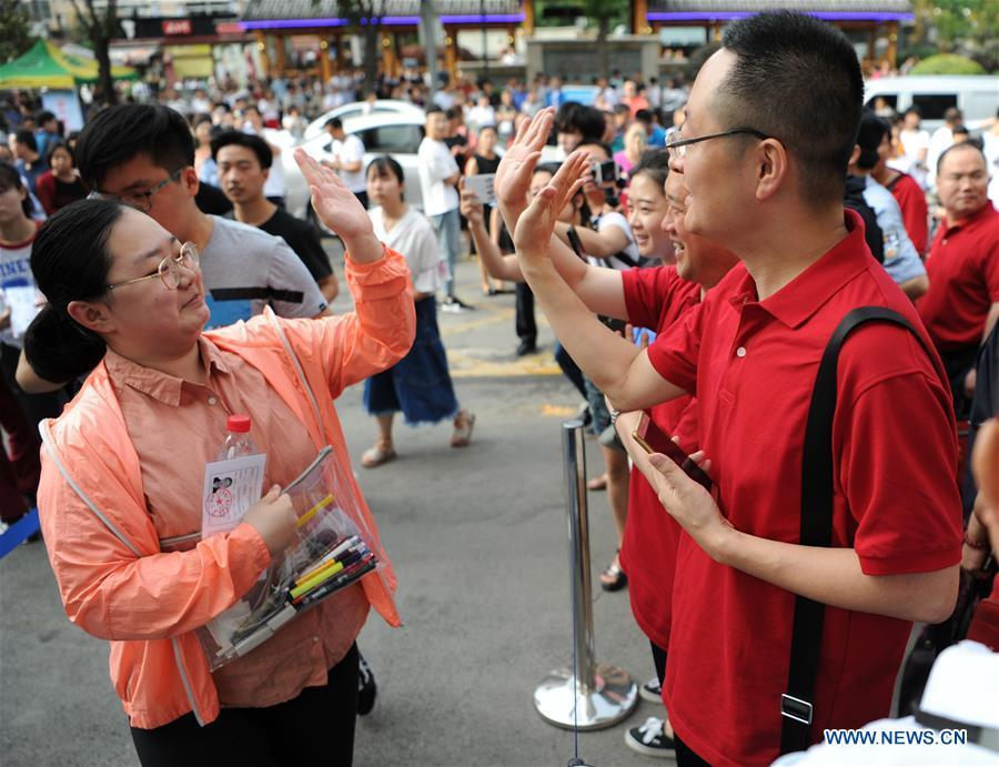 An examinee claps hands with her teacher before entering an exam venue in Xi\'an, capital of northwest China\'s Shaanxi Province, June 7, 2018. About 9.75 million students have registered for the national college entrance examination, which takes place from June 7 to 8. (Xinhua/Zhang Bowen)