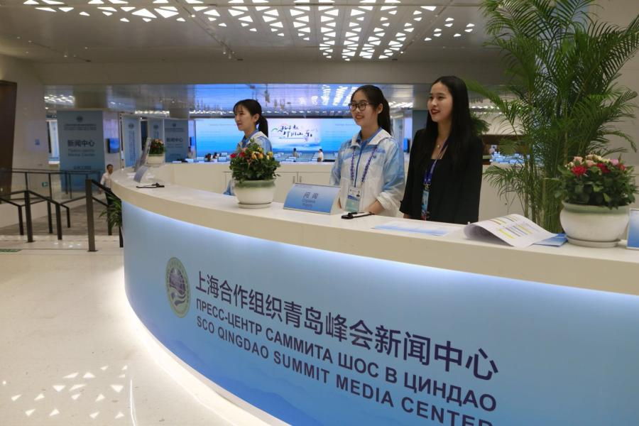 Volunteers work at the media center reception desk of the 18th Shanghai Cooperation Organization Summit in Qingdao, East China\'s Shandong Province, on June 7, 2018. (Photo: Li Hao/GT)