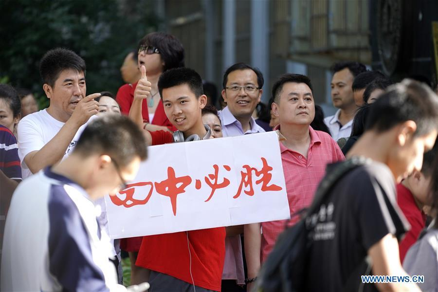 A student encourages examinees at an exam venue in Beijing, capital of China, June 7, 2018. About 9.75 million students have registered for the national college entrance examination, which takes place from June 7 to 8. (Xinhua/Shen Bohan)