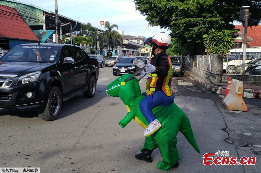 Thai police sergeant Tanit Bussabong directs traffic wearing a costume where he appears to ride a T-rex dinosaur outside a school in Nakhon Nayok on June 4, 2018. Bussabong, who has around 20 different outfits including Minnie Mouse and a bear for his traffic duty outside the kindergarten, said his prehistoric uniform is teaching kids road safety and convincing parents to obey traffic laws.  (Photo/Agencies)