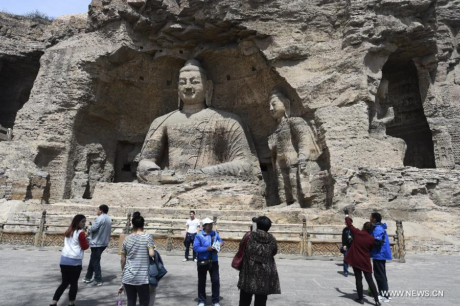 Tourists visit the Yungang Grottoes in Datong, north China\'s Shanxi Province, April 22, 2015. The Yungang Grottoes, listed as a UNESCO World Cultural Heritage site in 2001, will witness a tourism peak as the May Day holiday is coming. (Photo: Xinhua/Yan Yan)