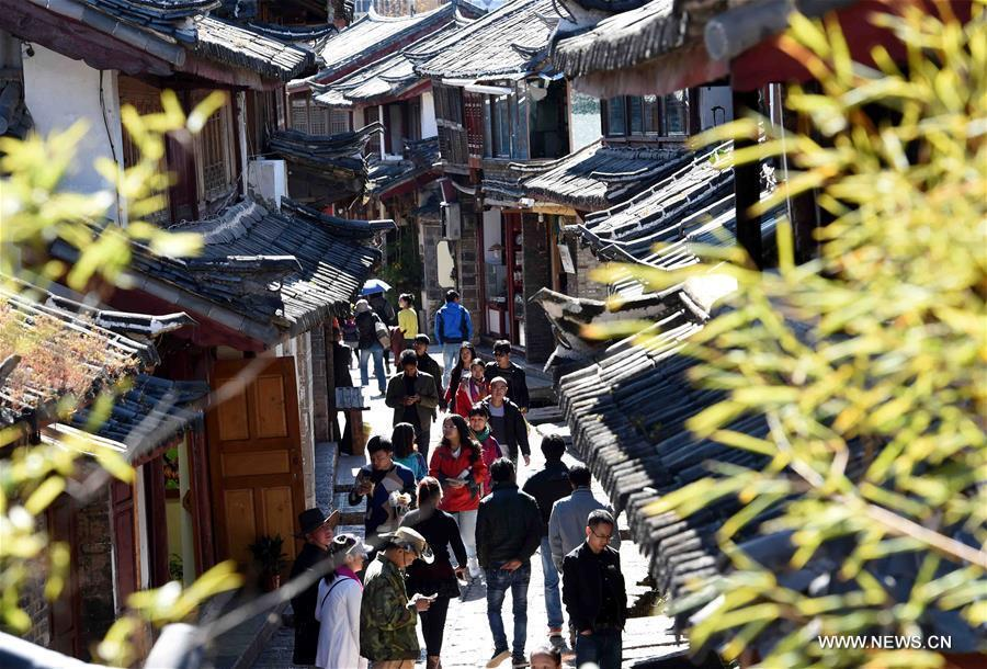 People walk in the street in Lijiang ancient town, southwest China\'s Yunnan Province, Nov. 16, 2015. Lijiang ancient town was listed as a world cultural heritage site by the UNESCO in 1997. (Photo: Xinhua/Yang Zongyou)