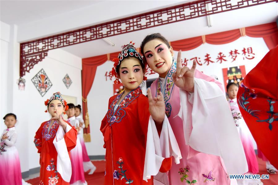 A teacher teaches students basic performing actions of Chinese drama at a primary school in Neiqiu County, north China\'s Hebei Province, June 8, 2018. The school introduced Chinese drama to student class to make it a way of inheriting traditional Chinese culture. (Xinhua/Zhu Xudong)