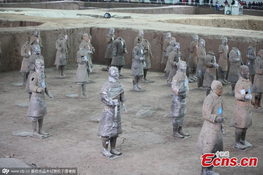 Life-sized terracotta warrior figures are seen clad in plastic greenhouse film, resembling \