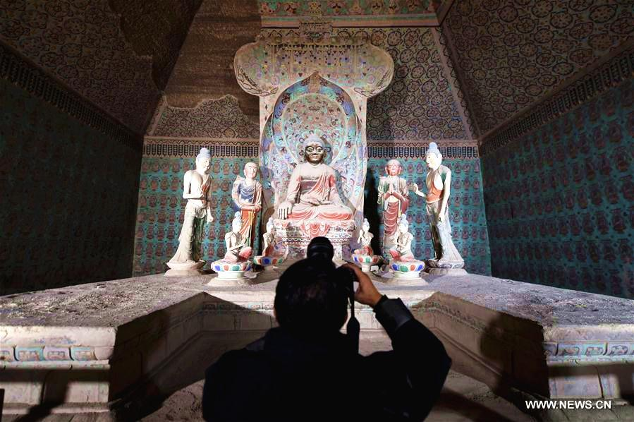 A photographer works in a cave in the Mogao Grottoes in Dunhuang, northwest China\'s Gansu Province, Oct. 10, 2016.(Photo/Xinhua)