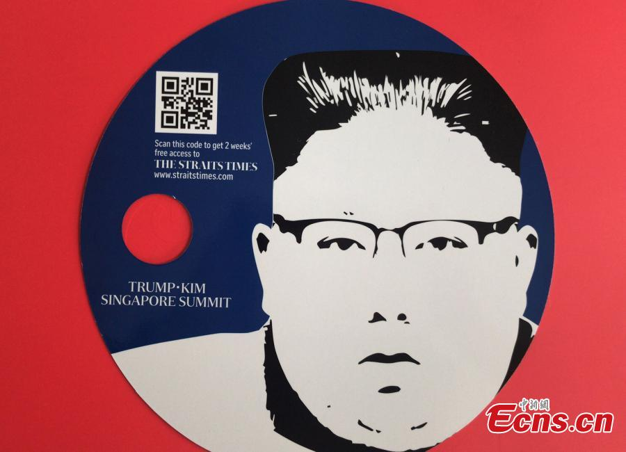 Souvenirs made for the DPRK-USA summit, including a notebook and a fan, are seen at the International Media Center at F1 Pit Building in Singapore, June 10, 2018. (Photo: China News Service/Meng Xiangjun)
