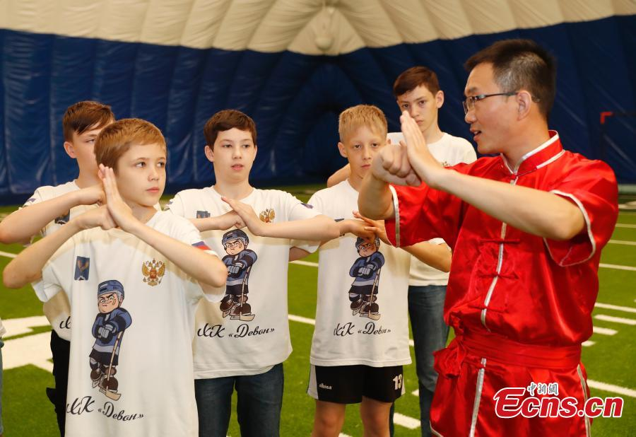 Russian teenager ice hockey players learn about kung fu during a visit to Beijing Huijia Private School in Beijing, June 11, 2018. (Photo: China News Service/Liu Guanguan)