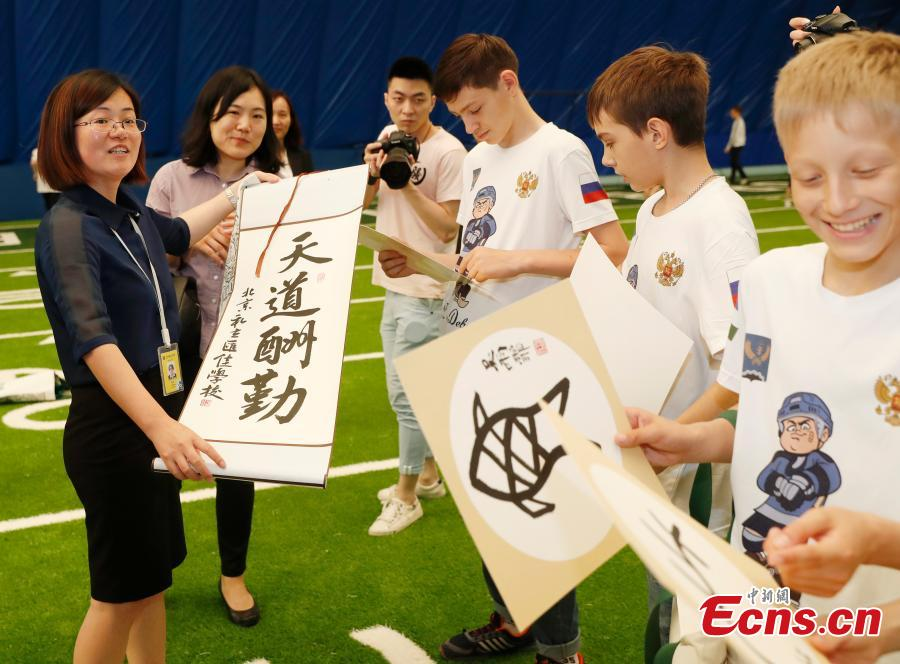 Zhang Ye, principal of Beijing Huijia Private School, presents gifts to visiting Russian teenager ice hockey players in Beijing, June 11, 2018. (Photo: China News Service/Liu Guanguan)