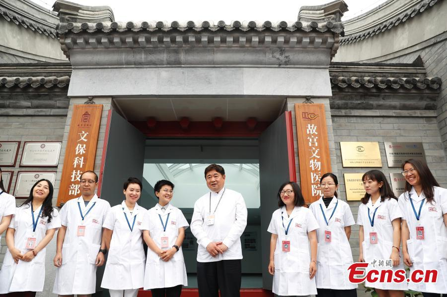 Shan Jixiang (C), the curator of the Palace Museum, poses with volunteers at the opening of its restoration \'hospital\' to the public in Beijing, June 9, 2018. As part of ongoing activities held for China\'s Cultural and Natural Heritage Day, the first batch of 40 people watched \'doctors\' repairing pieces from some of the museum\'s collections, including pieces of calligraphy, paintings, bronzeware and clocks, under the guidance of volunteers. Established in December 2016, the restoration hospital is located in the west of the Palace Museum. The facility covers 13,000 square meters and has the nation\'s most-advanced restoration studios. (Photo: China News Service/Liu Guanguan)