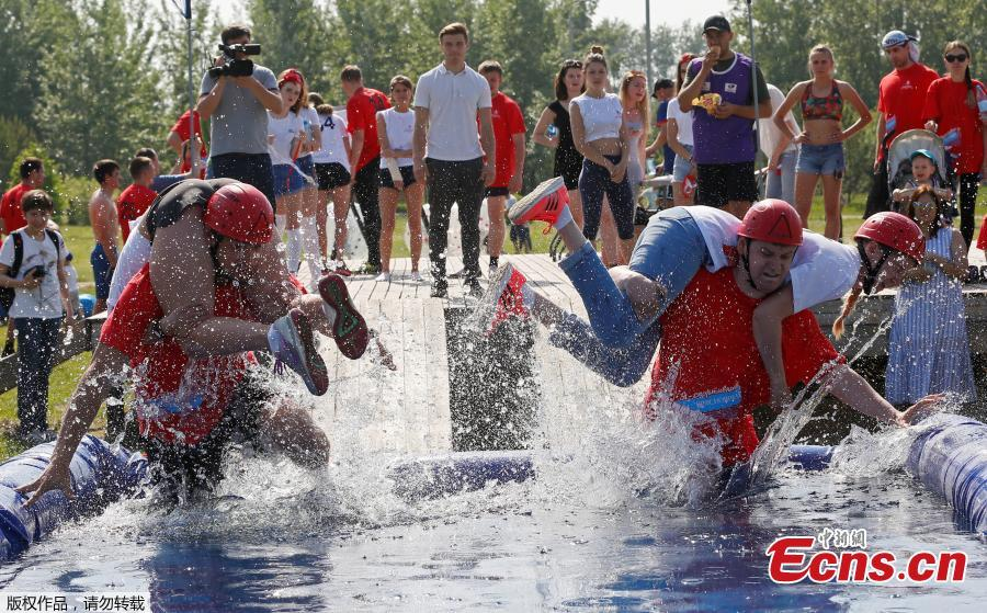 Men carry their wives over a water obstacle while racing in the Wife Carrying competition to mark the City Day in Krasnoyarsk, Russia, June 10, 2018. (Photo/Agencies)