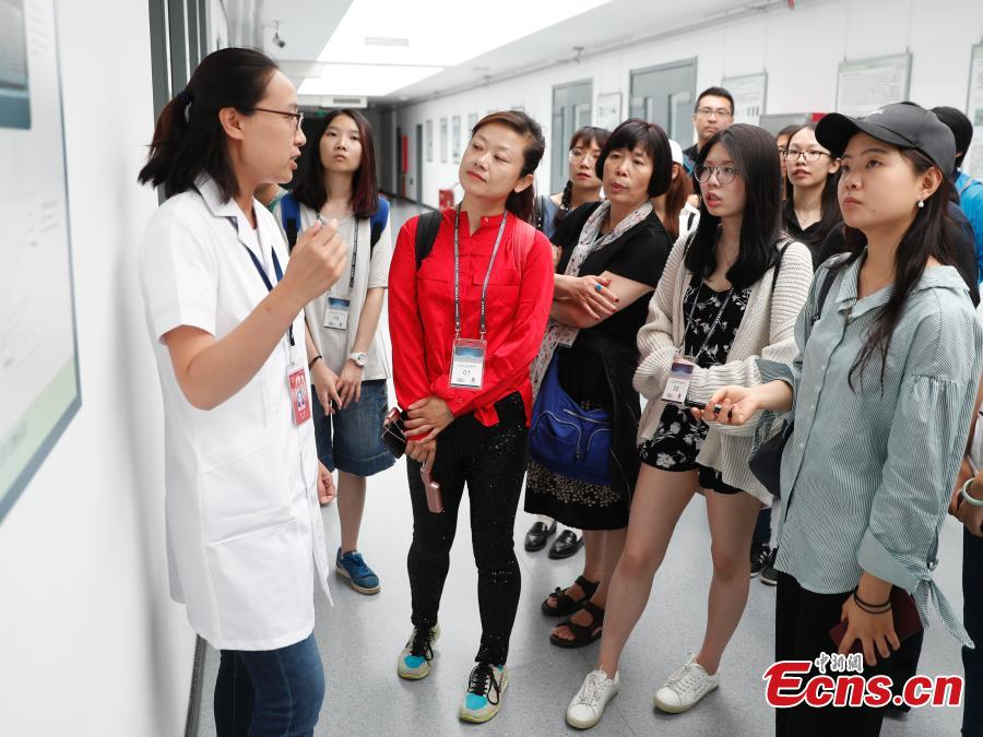 A volunteer talks to visitors about cultural relics restoration at a \'hospital\' in the Palace Museum in Beijing, June 9, 2018. As part of ongoing activities held for China\'s Cultural and Natural Heritage Day, the first batch of 40 people watched \'doctors\' repairing pieces from some of the museum\'s collections, including pieces of calligraphy, paintings, bronzeware and clocks, under the guidance of volunteers. Established in December 2016, the restoration hospital is located in the west of the Palace Museum. The facility covers 13,000 square meters and has the nation\'s most-advanced restoration studios. (Photo: China News Service/Liu Guanguan)