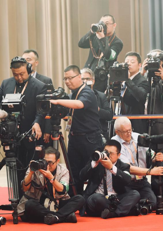 Journalists cover the SCO Qingdao Summit on Sunday. (Photo/China Daily)