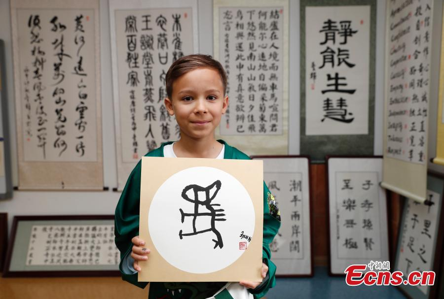 A Russian teenager ice hockey player shows a Chinese calligraphy work during a visit to Beijing Huijia Private School in Beijing, June 11, 2018. (Photo: China News Service/Liu Guanguan)