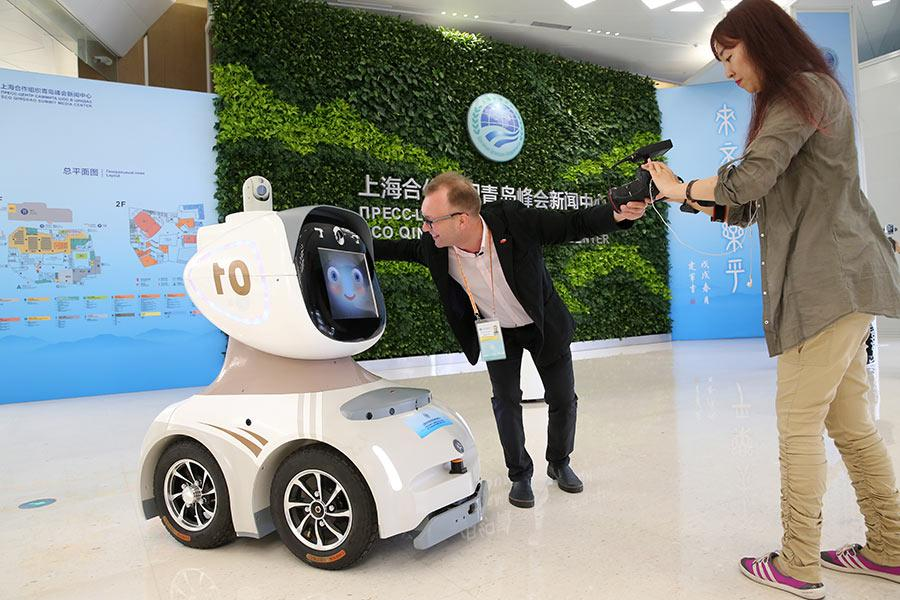 Journalists photograph a security robot at the news center of the summit on Friday.  (Photo/China Daily)