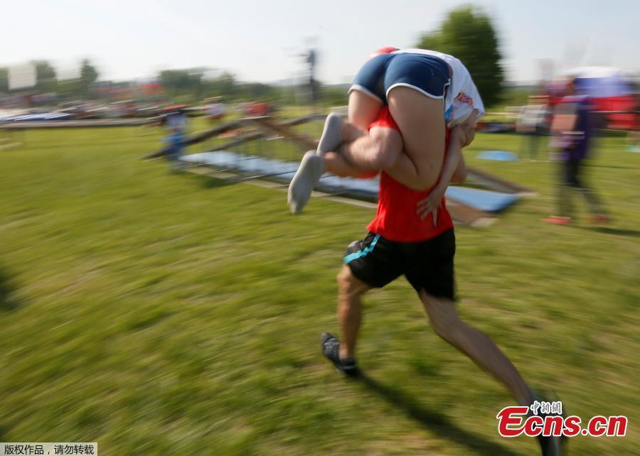 A man carries his wife while racing in the Wife Carrying competition to mark the City Day in Krasnoyarsk, Russia, June 10, 2018. (Photo/Agencies)