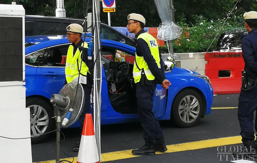 Singaporean police check the passing vehicles outside the St. Regis hotel where DPRK leader Kim Jong-un has stayed on Sunday. (Photo: Yang Sheng/GT)