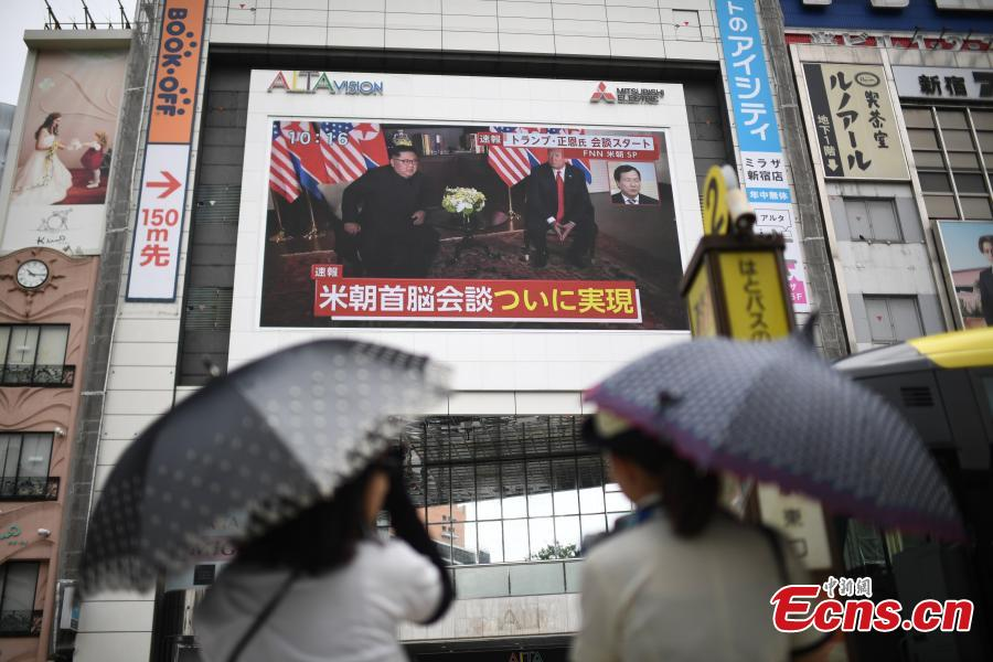 People watch a TV screen showing U.S. President Donald Trump meeting with the Democratic People\'s Republic of Korea (DPRK) leader Kim Jong Un in Singapore during a news program at a square in Tokyo, Japan, June 12, 2018. (Photo/Agencies)