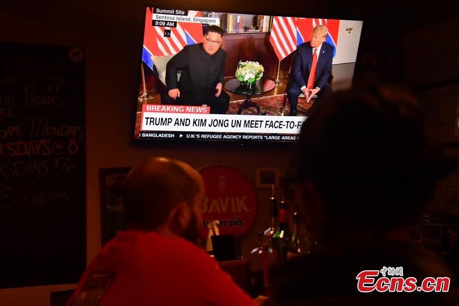 People watch a TV screen showing U.S. President Donald Trump meeting with the Democratic People\'s Republic of Korea (DPRK) leader Kim Jong Un in Singapore during a news program at a bar in Washington, the U.S., June 12, 2018. (Photo/Agencies)