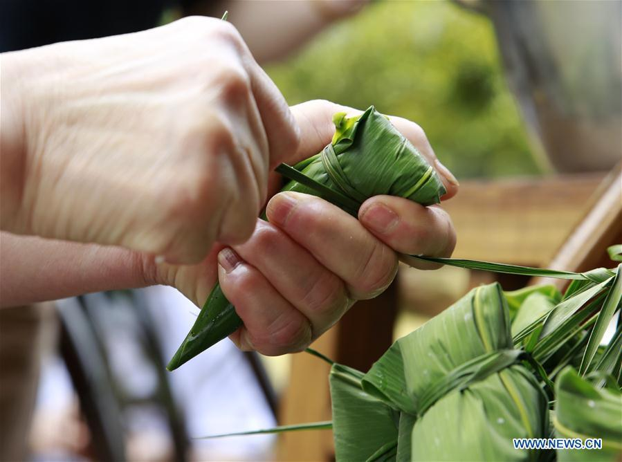 A resident makes Zongzi, a pyramid-shaped dumpling made of glutinous rice wrapped in bamboo or reed leaves, to greet the upcoming Dragon Boat Festival in Zhangjiajie City, central China\'s Hunan Province, June 11, 2018. (Xinhua/Wu Yongbing)
