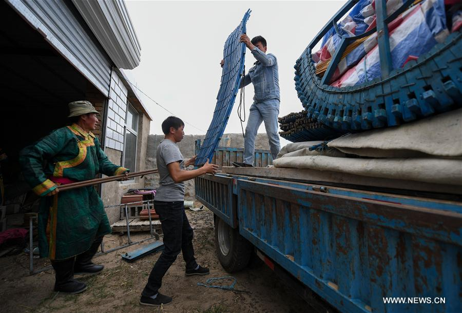 Erden uploads living households on truck with the help of relatives before transfer at the Ar Horqin Banner in Chifeng City, north China\'s Inner Mongolia Autonomous Region, June 4, 2018. June 5 was the day for Erden\'s family to move their cattle to a summer pasture, about 40 kilometers away from their family. It is a tradition for nomadic herdsmen spending their lives following the water and pasture. The transfer provides cattle and sheep abundant food and enables the grassland to renew itself. Erden and his sister drive their trucks loaded with living households and lead over 80 cattle towards the summer pasture. After 12 hours\' arduous journey, they arrived at their destination and prepared to set up yurt. They will stay here for a whole summer and return to their family in September. (Xinhua/Peng Yuan)