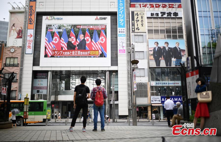 People watch a TV screen showing U.S. President Donald Trump meeting with the Democratic People\'s Republic of Korea (DPRK) leader Kim Jong Un in Singapore during a news program, at a square in Tokyo, Japan, June 12, 2018. (Photo/Agencies)